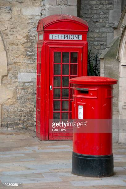 iconic red british mailbox and phone booth in front of brick wall in oxford, england - red stock pictures, royalty-free photos & images