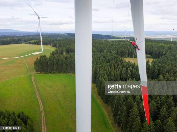 iconisch uitzicht op high rise rope access technician inspectie van blade op windturbine - hoog stockfoto's en -beelden