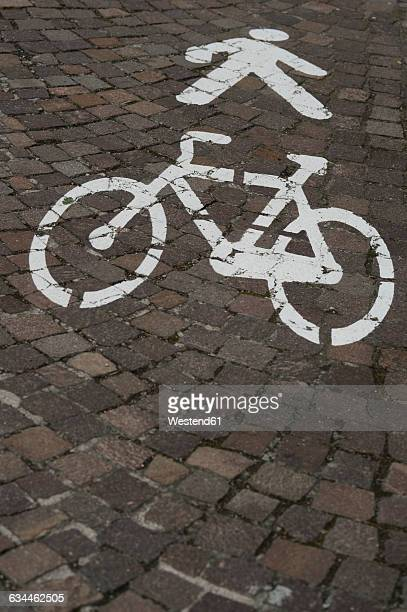 Icons for pedestrians and cyclists on cobblestone pavement