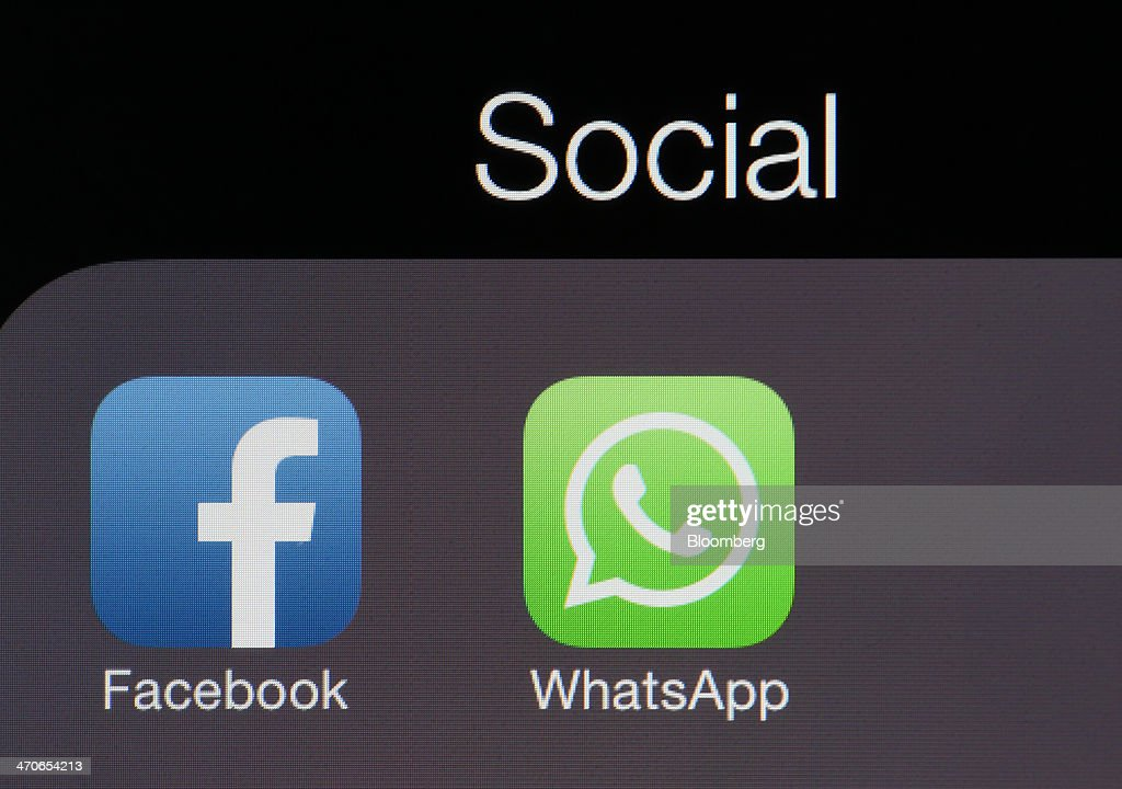 Icons for the WhatsApp Inc. mobile-messaging application WhatsApp and the Facebook Inc. application are displayed in a social media folder on the screen of an Apple Inc. iPhone in this arranged photograph taken in London, U.K., on Thursday, Feb. 20, 2014. Facebook, the worlds largest social network, agreed to acquire mobile-messaging startup WhatsApp Inc. for as much as $19 billion in cash and stock, seeking to expand its reach among users on mobile devices. Photographer: Chris Ratcliffe/Bloomberg via Getty Images