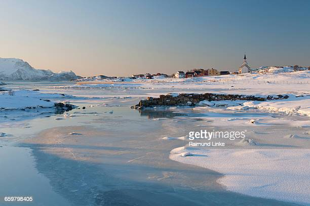 Icy coastal landscape with little town