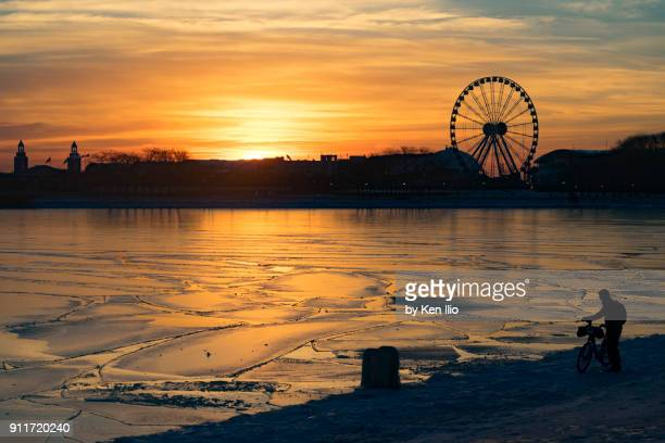 Icy lake water at sunrise with bicylist in foreground