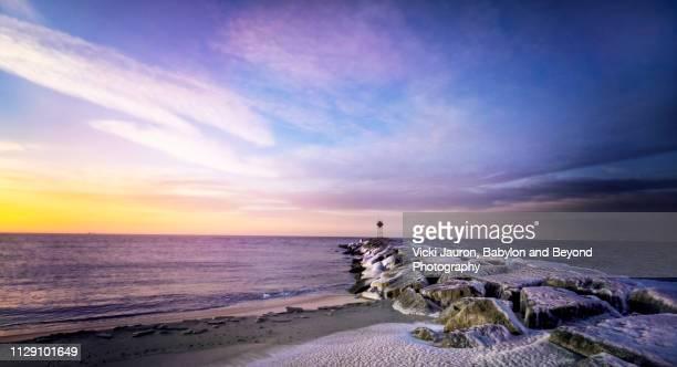 icy pier and dramatic sky at jones beach, long island - jones beach stock-fotos und bilder