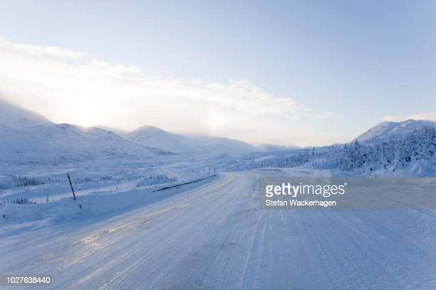 icy road, south klondike highway near fraser, snow covered alpine landscape, white pass, coastal range connecting skagway, alaska with british columbia, canada - paisajes de alaska fotografías e imágenes de stock