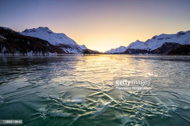 icy surface of lake sils at sunset. - swiss alps stock pictures, royalty-free photos & images