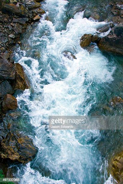 Icy water from snowmelt rushes through a mountain gorge between boulders in the Himalaya.