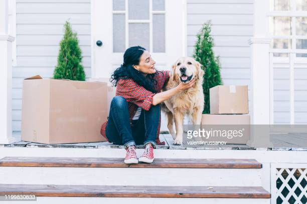 新しい家に移動し、階段に座って、彼女のゴールデンレトリバーをかわいがる大人の女性 - 一匹 ストックフォトと画像
