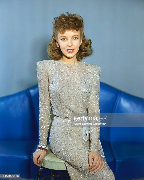 Ida Lupino British actress wearing a grey dress and sitting on a stool in a studio portrait against a blue background circa 1950