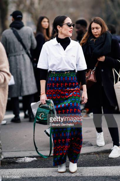 Idalia Salsamendi wears sunglasses earrings a black turtleneck a Lacoste white polo shirt a green Chloé bag a colorful long skirt white boots outside...