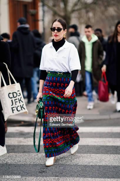 Idalia Salsamendi wears sunglasses earrings a black turtleneck a Lacoste white polo shirt a green bag a colorful long skirt white boots outside...