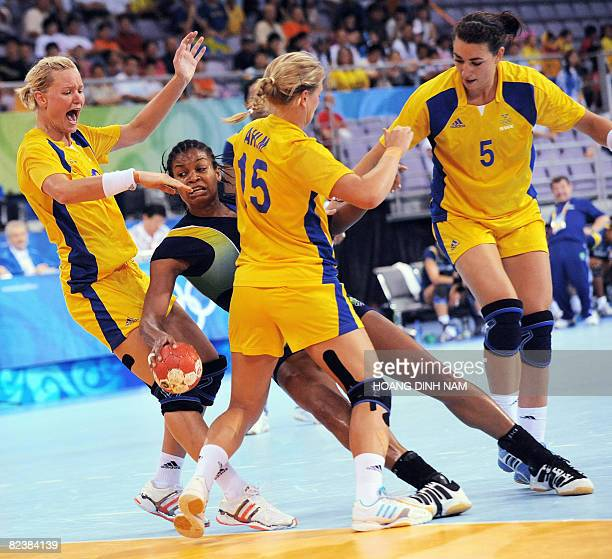 Idalina Mesauita of Brazil tries to shoot as Annika Wiel Freden Johanna Ahlm and Sara Holmgren of Sweden stop her in their Beijing 2008 Olympic Games...