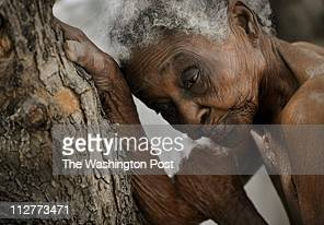 Idamise Pierre leans against a tree for support as she waits to bathe at the cityrun nursing home for the aging population in PortauPrince
