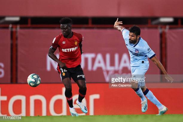 Iddrisu Mohamed Baba of RCD Mallorca competes for the ball with Diego Costa of Atletico de Madrid during the La Liga match between RCD Mallorca and...