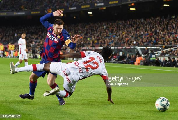 Iddrisu Mohamed Baba of RCD Mallorca is challenged by Lionel Messi of FC Barcelona during the Liga match between FC Barcelona and RCD Mallorca at...