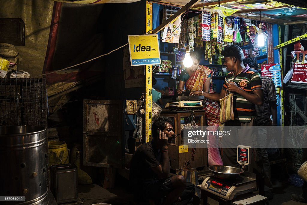 Idea Cellular Ltd. signage is displayed as a vendor serves customers at a store in the Anandapur area of Kolkata, West Bengal, India, on Friday, Nov. 1, 2013. Indian stocks fell for the first time in six days, led by technology and consumer companies, after benchmark indexes climbed to records in a holiday trading session on Nov. 3. Photographer: Sanjit Das/Bloomberg via Getty Images