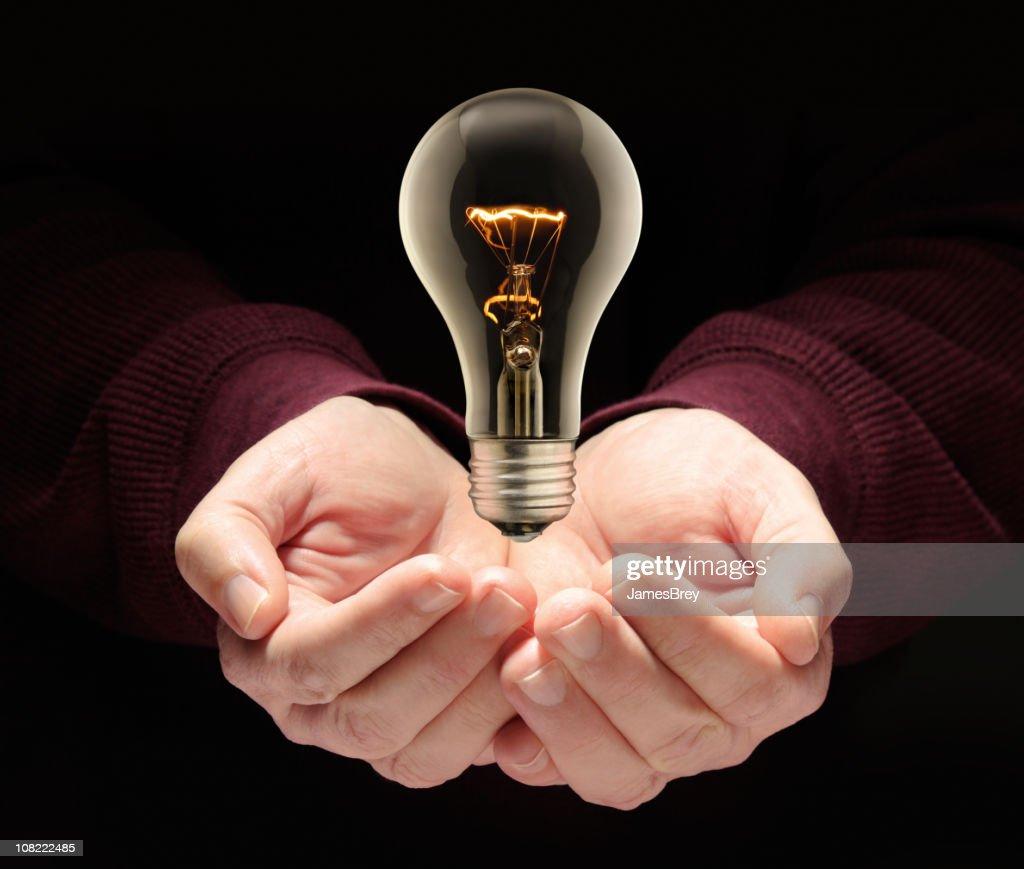 Idea Light Bulb Levitating Illuminated Over Nurturing Hands, Black Background : Bildbanksbilder