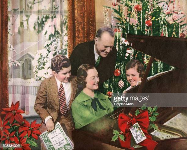 Idealized American couple with their two children singing Christmas carols around the piano and Christmas tree on Christmas Day 1937 Screen print...