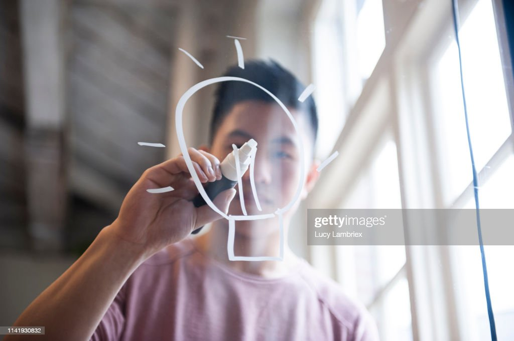 Ideas! Fifteen year old boy drawing a lightbulb on glass with a chalk marker : Stock Photo