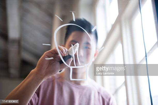 ideas! fifteen year old boy drawing a lightbulb on glass with a chalk marker - ideas stock pictures, royalty-free photos & images