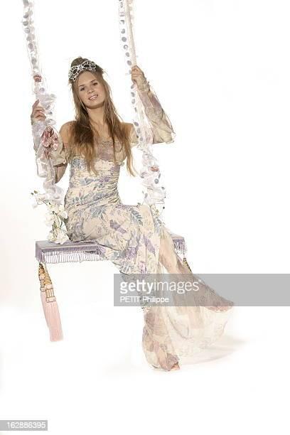 Ideas For Christmas Gifts For The Whole With Family. Le conte de fées de Noël : Laetitia, princesse romantique assise sur une balancelle, portant une...