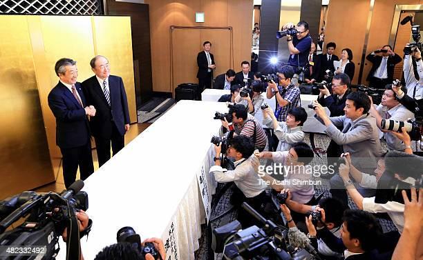 Idemitsu Kosan CEO Takashi Tsukioka and Showa Shell Sekiyu CEO Tsuyoshi Kameoka shake hands during a press conference on July 30 2015 in Tokyo Japan...