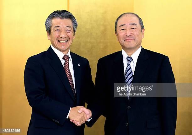 Idemitsu Kosan CEO Takashi Tsukioka and Showa Shell Sekiyu CEO Tsuyoshi Kameoka shake hands during the press conference on July 30 2015 in Tokyo...