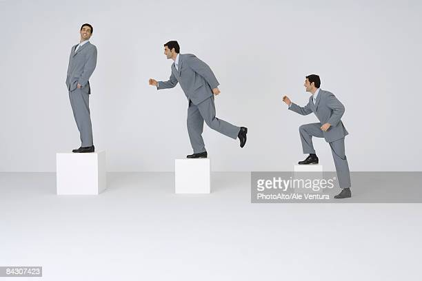 identical businessmen climbing gradually larger blocks - grey suit stock pictures, royalty-free photos & images