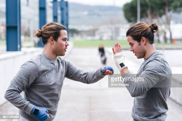 identical male adult twin boxers training outdoors, practicing punches - man bun stock pictures, royalty-free photos & images