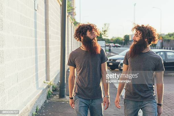 Identical male adult twins strolling and chatting on sidewalk