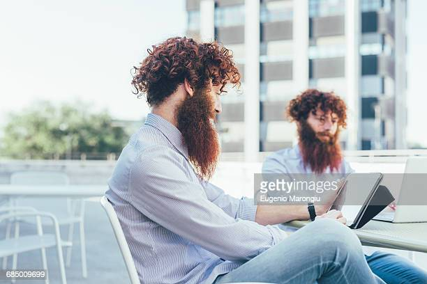 Identical male hipster twins using digital tablet on apartment roof terrace