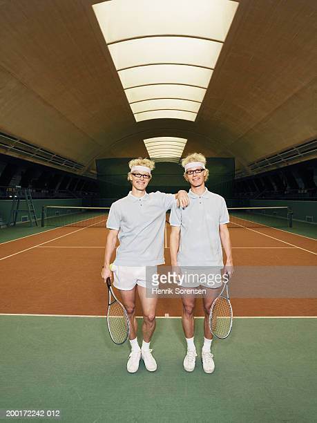 Identical male twins holding rackets by tennis court