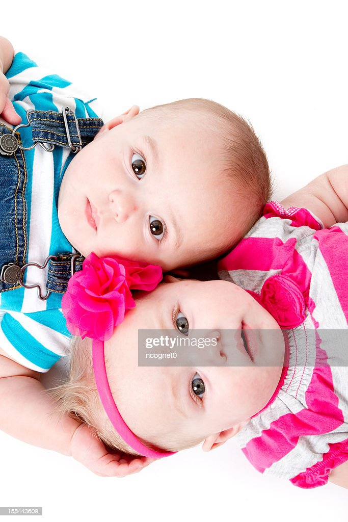Identical twin babies lying in opposite directions : Stock Photo