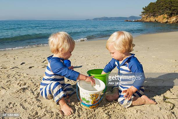Identical twin boy toddlers play on the beach