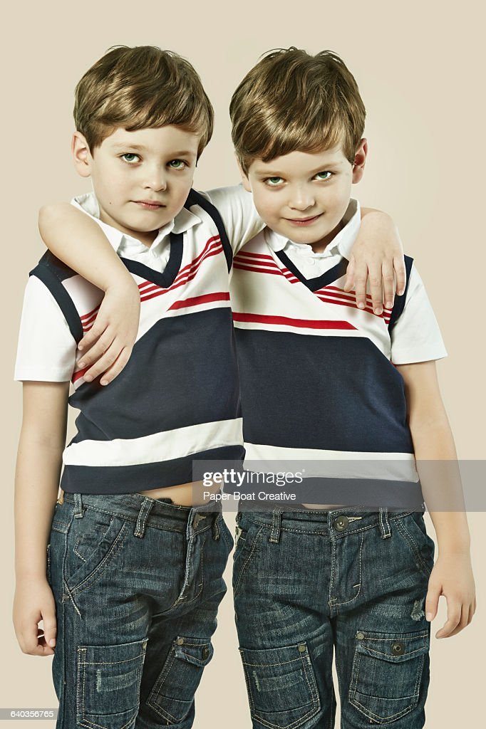 identical twin brother standing next to each other stock photo