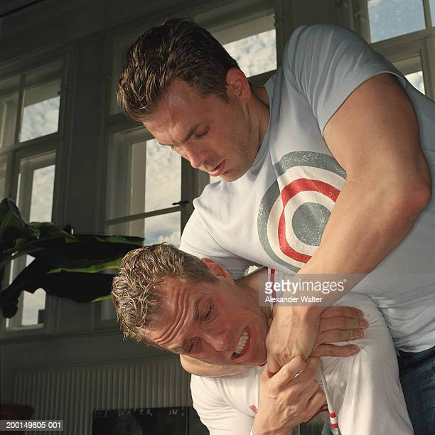 identical twin brothers wrestling, one with other in headlock - restraining stock photos and pictures