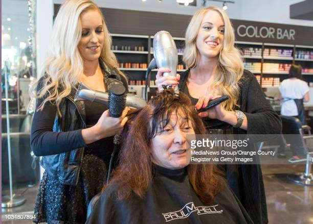 Identical twin sisters Kellie Lynn Wilson left and Kristyn Lee Wilson work on the hair of client Anna Cooper of Long Beach at Paul MItchell The...