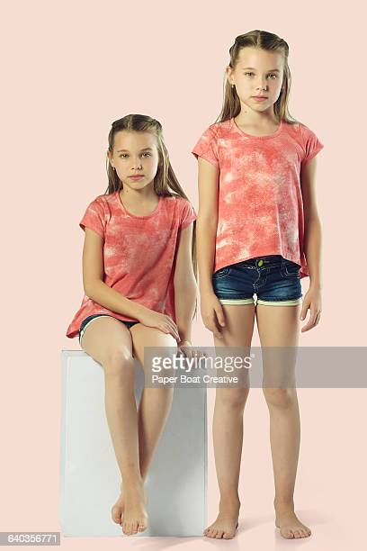 Identical twin sisters standing next to each other