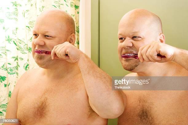Identical twins brushing teeth