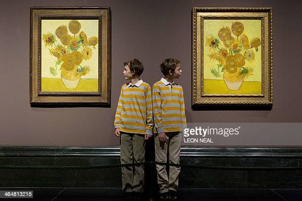 Identical twins Edgar and Gabriel pose for photographs with two version of Dutch artist Vincent van Gogh's Sunflowers paintings at the National...