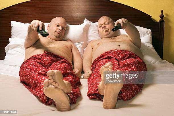 Identical twins relaxing in bed