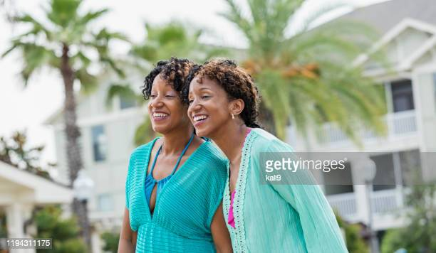 identical twins standing together, watching something - identical twin stock pictures, royalty-free photos & images