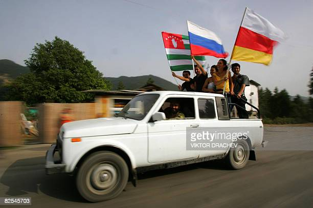 Identifiers - South Ossetians wave the flags of Russia, South Ossetia , and Abkhazia while riding in a vehicle 35 km form Tskhinvali near village...