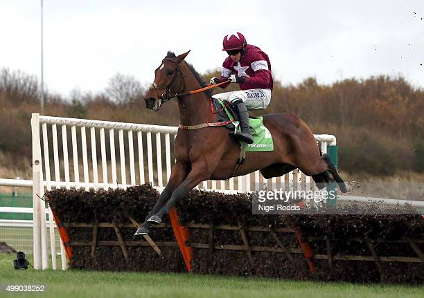 Identity Thief riden by Bryan Cooper jumps the last hurdle to win The StanJamescom Fighting Fifth Hurdle race at Newcastle racecourse on November 28...