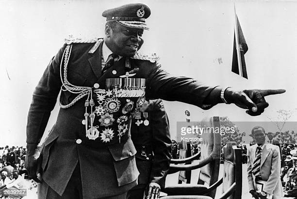 Idi Amin President of Uganda, with all his medals, points a finger during an outdoor rally.