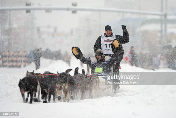 Iditarod champion John Baker and his Iditarider wave during the start of the 2012 Iditarod Trail Sled Dog Race in Anchorage Alaska Saturday March 3...