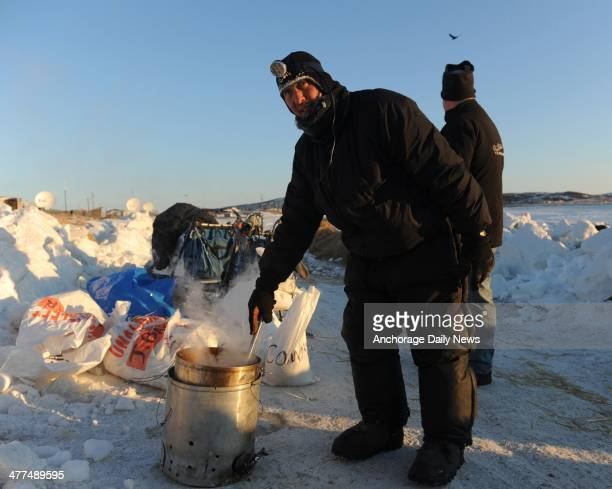 Iditarod musher John Baker from Kotzebue Alaska prepares dog food for his team at the Unalakleet checkpoint at sunrise during the Iditarod Trail Sled...