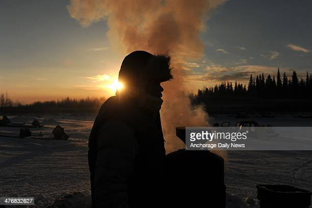 Iditarod musher Newton Marshall gets hot water from the wood fired heater at the Nikolai checkpoint during the 2014 Iditarod Trail Sled Dog Race at...