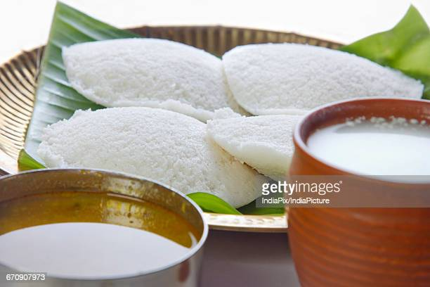 Idli in a plate with sambar and lassi