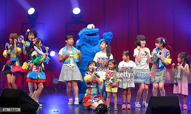Idol group AKB48 and perform onstage with Elmo and Cookie Monster at the Universal Studios Japan on July 21 2016 in Osaka Japan