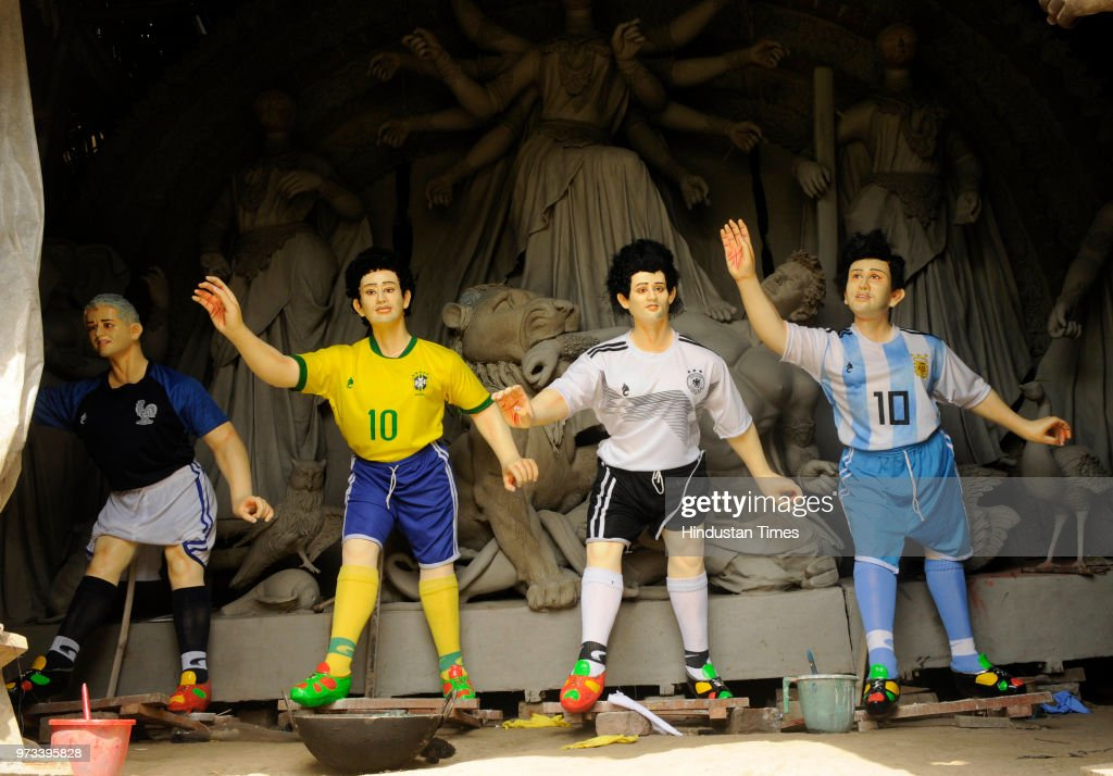 Idol makers carry idols of some of the icon footballers like Messi, Neimar and Ronaldo and a replica of World Cup to a fan club at Baghajatin, on June 13, 2018 in Kolkata, India. Fans from different parts of the city of Kolkata, which is known as Mecca of Indian Football, gear up to cheer up their team and the idol players from different countries on the occasion of upcoming World Cup Football Tournament, which is going to begin from tomorrow in Russia.